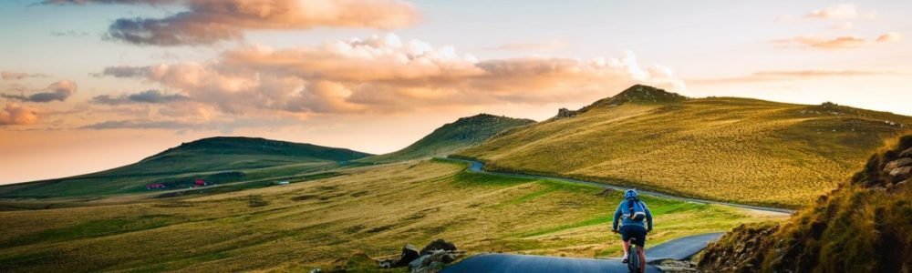 rear-view-of-man-on-mountain-road-against-sky-258045